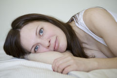 serious woman lying on bed Stock Photography