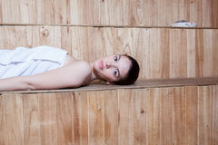 Serious woman lying inside the sauna Stock Photography