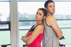 Serious woman and man standing back to back in gym Royalty Free Stock Photography