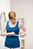Serious woman measuring her waist. Serious woman checking dieting success by measuring her waist with measuring tape Royalty Free Stock Photo