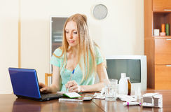 Serious  woman with medications and laptop Royalty Free Stock Images