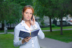 Serious woman with notebook talking on the phone Stock Photography