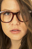 Serious woman peering through her hair wearing glasses Stock Images