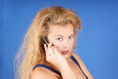 Serious woman on the phone. Serious blond woman on mobile phone receiving bad news. Studio shot on light blue background Stock Photo