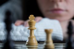 Woman Watching Chessboard. Serious Woman Playing Chess Watching the Chessboard Royalty Free Stock Image