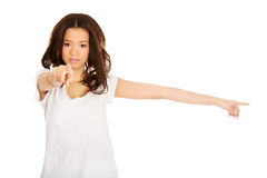 Serious woman pointing on you and aside. Royalty Free Stock Photography