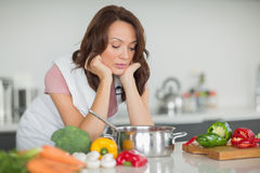 Serious woman preparing food in kitchen Stock Photo
