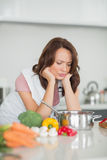 Serious woman preparing food in kitchen Royalty Free Stock Images