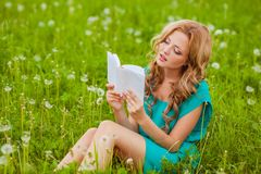 Serious woman reading book outdoors. Serious woman sitting reading book outdoors Stock Image