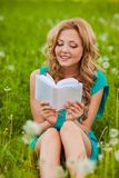Serious woman reading book outdoors Royalty Free Stock Photo