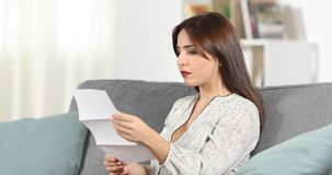 Serious woman reading a letter at home. Serious woman reading a letter sitting on a couch in the living room at home