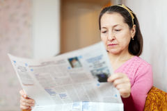 Serious woman reading newspaper Royalty Free Stock Image