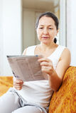 Serious  woman reading newspaper Stock Photos
