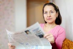 Serious woman reading newspaper Stock Photo