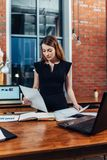 Serious woman reading papers studying resumes standing at work desk in stylish office.  Stock Photos