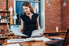 Serious woman reading papers studying resumes standing at work desk in stylish office Stock Photos