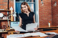 Serious woman reading papers studying resumes standing at work desk in stylish office.  stock photo