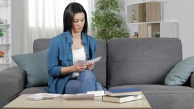 Serious woman reading a receipt at home stock footage