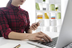 Serious woman in red checkered shirt is working at her laptop an Royalty Free Stock Photos