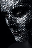 Serious woman with rhinestone skull on face. In dark Stock Photos