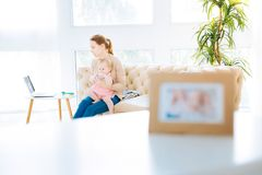 Concentrated woman sitting with a little daughter Stock Photography