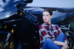 Serious woman in a shirt on a motorcycle background, smoothed hair and red lipstick stock photos