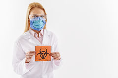 Serious woman showing dangerous symbol. We are in danger. Concentrated female scientist is holding toxic contamination sign. Portrait. Isolated and copy space Stock Image