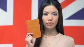 Serious woman showing passport, Great Britain flag, business trip to England. Stock footage stock video footage