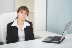 Serious woman sits at light office with laptop. The serious woman sits at a table at light office with the laptop stock image