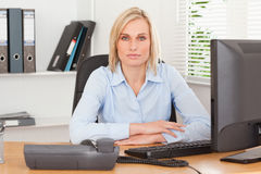 Serious woman sitting behind a desk. In an office Royalty Free Stock Photos