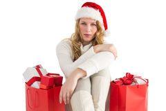 Serious woman sitting on floor with shopping bag. On white background Stock Images