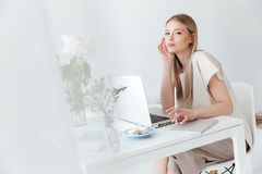 Serious woman sitting indoors using laptop Royalty Free Stock Photos