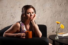 Serious Woman Sitting with Mug Stock Photos
