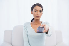 Serious woman sitting on sofa changing tv channel Royalty Free Stock Photos