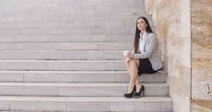 Serious woman sitting on stairs outdoors Stock Photo