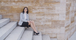 Serious woman sitting on stairs outdoors Royalty Free Stock Photography