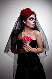 Serious woman in skull face art mask and flowers. Young woman wearing with roses dressed up for All Souls Day with flowers royalty free stock photography