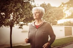 Serious woman in sports clothing jogging trough city park. stock photography