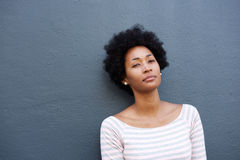 Serious woman standing alone against gray wall Royalty Free Stock Photos