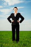 Serious woman standing at the green field Royalty Free Stock Photography