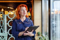 A serious woman, stands near the window and holds a clipboard, writes something there and looks into the distance. Royalty Free Stock Photos