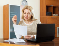 Serious woman staring financial documents Stock Image