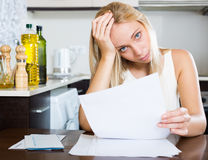 Serious woman staring financial documents. At table in home Stock Image