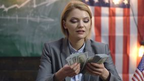 Serious woman in a suit counts money. Economy and finance. Woman with dollar money for bribe. Independence day of usa. Income planning of budget increase stock footage