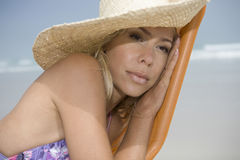 Serious Woman In Sunhat On Deckchair At Beach Stock Photography