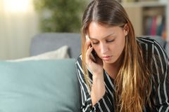 Free Serious Woman Talking On Phone On A Sofa At Home Stock Images - 165765054