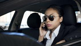 Serious woman talking on phone in car, private detective spying, police agent. Stock photo royalty free stock images