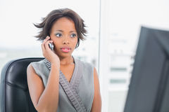 Serious woman talking on phone while looking at computer screen Stock Photos
