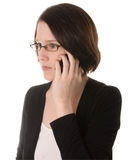 Serious woman talks on phone. A serious woman talks on a mobile phone or cellphone Royalty Free Stock Photography