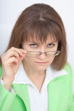 Serious woman - teacher looks at us over glasses Stock Image